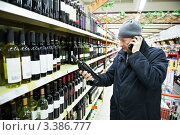 Купить «Мужчина выбирает вино в супермаркете и разговаривает по сотовому телефону», фото № 3386777, снято 31 декабря 2011 г. (c) Дмитрий Калиновский / Фотобанк Лори