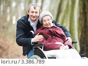 Купить «Мужчина гуляет в парке с пожилой женщиной в инвалидном кресле», фото № 3386789, снято 1 января 2012 г. (c) Дмитрий Калиновский / Фотобанк Лори