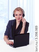 Молодая бизнес-леди работает с гарнитурой и компьютером на рабочем месте. Стоковое фото, фотограф Симон Герреро Ушаков / Фотобанк Лори