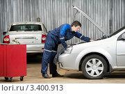 Купить «Автомеханинк стоит перед открытым капотом автомобиля», фото № 3400913, снято 31 марта 2012 г. (c) Дмитрий Калиновский / Фотобанк Лори