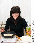 Купить «Весёлая женщина готовит блины  на переносной плите», эксклюзивное фото № 3413273, снято 25 февраля 2012 г. (c) Игорь Низов / Фотобанк Лори