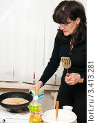 Купить «Женщина готовит блины на чугунной сковородке на переносной плите», эксклюзивное фото № 3413281, снято 25 февраля 2012 г. (c) Игорь Низов / Фотобанк Лори