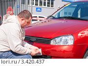 Купить «Покупка автомобиля, мужчина прикручивает регистрационные номера на купленный автомобиль», фото № 3420437, снято 30 марта 2012 г. (c) Рожков Юрий / Фотобанк Лори