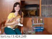 Купить «Веселая девушка с кошкой на руках сидит дома рядом с попугаем в клетке и змеей в аквариуме. В шкафу аквариум с рыбками», фото № 3424249, снято 29 марта 2012 г. (c) Яков Филимонов / Фотобанк Лори
