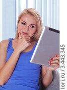 Красивая девушка читает свой компьютер планшет сидя у себя дома. Стоковое фото, фотограф Симон Герреро Ушаков / Фотобанк Лори