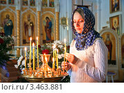 Купить «Девушка ставит свечку в православном храме», фото № 3463881, снято 13 апреля 2012 г. (c) Андрей Ярославцев / Фотобанк Лори