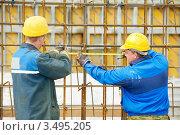 Купить «Два строителя измеряют металлическую конструкцию», фото № 3495205, снято 21 апреля 2012 г. (c) Дмитрий Калиновский / Фотобанк Лори