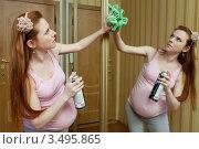 Купить «Беременная женщина дома протирает большое зеркало», фото № 3495865, снято 10 марта 2012 г. (c) Михаил Иванов / Фотобанк Лори