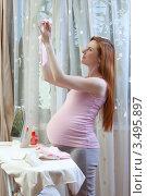 Купить «Беременная женщина гладит утюгом детскую одежду», фото № 3495897, снято 10 марта 2012 г. (c) Михаил Иванов / Фотобанк Лори