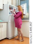 Купить «Беременная женщина на кухне около холодильника», фото № 3495957, снято 10 марта 2012 г. (c) Михаил Иванов / Фотобанк Лори