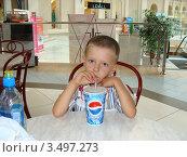 Мальчик за столиком в кафе пьет  пепси (2009 год). Редакционное фото, фотограф Валерий Борисенко / Фотобанк Лори