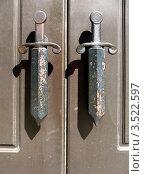 Купить «Фрагмент металлической двери с ручками в виде кинжалов», фото № 3522597, снято 15 мая 2012 г. (c) Заноза-Ру / Фотобанк Лори