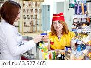 Купить «Покупательница на кассе расплачивается кредитной карточкой. Девушка-кассир улыбается и смотрит в камеру», фото № 3527465, снято 13 мая 2012 г. (c) Баевский Дмитрий / Фотобанк Лори