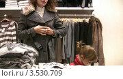 Купить «Мама с дочкой примеряют одежду в магазине», видеоролик № 3530709, снято 25 декабря 2008 г. (c) Losevsky Pavel / Фотобанк Лори