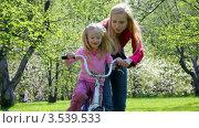 Купить «Мама учит дочку кататься на велосипеде в парке», видеоролик № 3539533, снято 18 июня 2010 г. (c) Losevsky Pavel / Фотобанк Лори