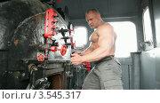 Купить «Бодибилдер с обнаженным торсом открывает печь локомотива», видеоролик № 3545317, снято 4 ноября 2009 г. (c) Losevsky Pavel / Фотобанк Лори