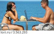 Купить «Мужчина с ноутбуком, женщина с телефоном за столом на фоне моря», видеоролик № 3563293, снято 23 января 2010 г. (c) Losevsky Pavel / Фотобанк Лори