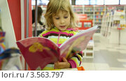 Купить «Девочка листает книгу в магазине», видеоролик № 3563797, снято 2 февраля 2010 г. (c) Losevsky Pavel / Фотобанк Лори