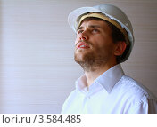 Молодой мужчина в белой каске смотрит вверх (2012 год). Редакционное фото, фотограф Оленька Винник / Фотобанк Лори