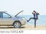 Недовольный мужчина пинает сломавшуюся автомашину на берегу моря. Стоковое фото, фотограф Elnur / Фотобанк Лори