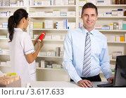 Купить «Женщина и мужчина работают за прилавком аптеки», фото № 3617633, снято 13 декабря 2011 г. (c) Monkey Business Images / Фотобанк Лори