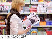 Купить «Девушка читает журнал в магазине», фото № 3634297, снято 11 марта 2011 г. (c) Losevsky Pavel / Фотобанк Лори