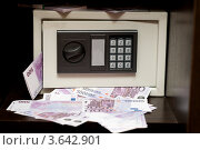 Домашний маленький электронный сейф с торчащими из него деньгами - банкнотами по 500 евро. Стоковое фото, фотограф katalinks / Фотобанк Лори