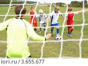 Дети играют в футбол, вратарь готовится ловить мяч. Стоковое фото, фотограф Monkey Business Images / Фотобанк Лори