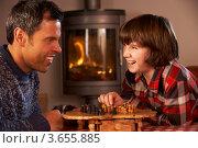 Купить «Отец с сыном перед камином играют в шахматы», фото № 3655885, снято 24 января 2012 г. (c) Monkey Business Images / Фотобанк Лори