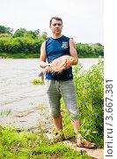 Купить «Счастливый рыбак с лещом в руках на фоне реки», эксклюзивное фото № 3667381, снято 12 июня 2012 г. (c) Игорь Низов / Фотобанк Лори