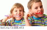 Купить «Мальчик и девочка в полосатых футболках чистят зубы», видеоролик № 3688413, снято 1 мая 2010 г. (c) Losevsky Pavel / Фотобанк Лори