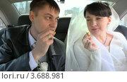 Купить «Жених с невестой едят печенье в машине», видеоролик № 3688981, снято 16 марта 2010 г. (c) Losevsky Pavel / Фотобанк Лори