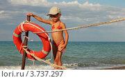 Девочка стоит у спасательного круга на берегу моря. Стоковое видео, видеограф Losevsky Pavel / Фотобанк Лори