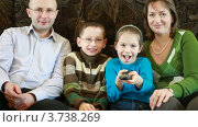 Купить «Члены семьи сидят и передают друг другу сломанный пульт дистанционного управления», видеоролик № 3738269, снято 26 мая 2007 г. (c) Losevsky Pavel / Фотобанк Лори