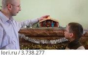 Отец стоит с сыном перед камином на Рождество. Стоковое видео, видеограф Losevsky Pavel / Фотобанк Лори