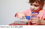 Купить «Маленькая девочка кладет камешки в модельку торговой корзины», видеоролик № 3739289, снято 30 мая 2011 г. (c) Losevsky Pavel / Фотобанк Лори