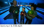 Купить «Мама, папа и сын держат шары для боулинга на фоне дорожек», видеоролик № 3739421, снято 11 августа 2011 г. (c) Losevsky Pavel / Фотобанк Лори