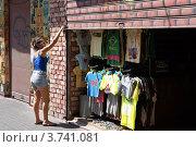Купить «Загорелая девушка в коротких шортах поднимает жалюзи в лавке одежды. Исторический район южного Тель-Авива.», фото № 3741081, снято 8 августа 2012 г. (c) Олег Хмельниц / Фотобанк Лори