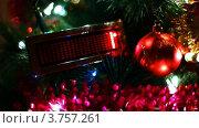 """Купить «Игрушечный стеклянный шар и экран с бегущей строкой """"С рождеством"""" висят на ветках новогодней елки, переливающейся огнями», видеоролик № 3757261, снято 30 сентября 2011 г. (c) Losevsky Pavel / Фотобанк Лори"""