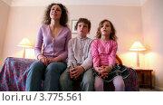Купить «Мама с сыном и дочкой сидят на диване и смотрят телевизор», видеоролик № 3775561, снято 20 марта 2012 г. (c) Losevsky Pavel / Фотобанк Лори