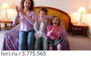 Купить «Мама с сыном и дочкой сидят на кровати, смотрят телевизор и хлопают в ладоши», видеоролик № 3775565, снято 14 марта 2012 г. (c) Losevsky Pavel / Фотобанк Лори