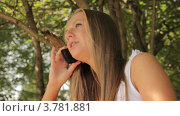 Девушка разговаривает по мобильному телефону, сидя в летнем парке. Стоковое видео, видеограф Максим Шатохин / Фотобанк Лори