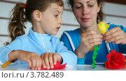 Купить «Мать показывает дочке, как делать бумажный цветок», видеоролик № 3782489, снято 2 июня 2012 г. (c) Losevsky Pavel / Фотобанк Лори