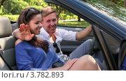 Купить «Молодой человек и девушка сидят на переднем сидении в кабриолете, смотрят друг на друга и улыбаются летним днем», видеоролик № 3782893, снято 30 апреля 2012 г. (c) Losevsky Pavel / Фотобанк Лори
