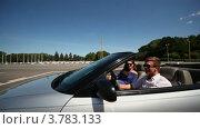 Купить «Молодой человек и девушка едут  в кабриолете по городу и улыбаются летним днем», видеоролик № 3783133, снято 30 апреля 2012 г. (c) Losevsky Pavel / Фотобанк Лори