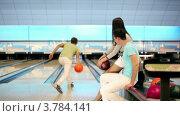 Купить «Парень с девушкой смотрят, как их друг бросает шар для боулинга», видеоролик № 3784141, снято 7 апреля 2012 г. (c) Losevsky Pavel / Фотобанк Лори