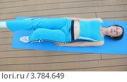 Купить «Женщина в голубом спортивном костюме лежит на ковре и сгибает ноги», видеоролик № 3784649, снято 24 июля 2012 г. (c) Losevsky Pavel / Фотобанк Лори
