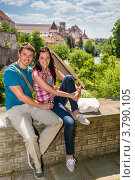 Счастливая молодая пара сидит на балконе на фоне достопримечательностей. Стоковое фото, фотограф CandyBox Images / Фотобанк Лори