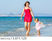 Купить «Счастливая мама с ребенком идут по пляжу на фоне моря», фото № 3811129, снято 4 апреля 2020 г. (c) Sergey Borisov / Фотобанк Лори