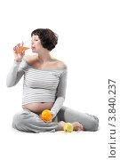 Беременная женщина сидит на полу с фруктами и натуральным соком на белом фоне. Стоковое фото, фотограф Vycheslav Leskovskiy / Фотобанк Лори